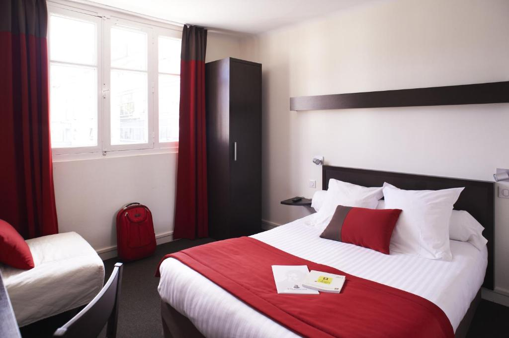 A bed or beds in a room at Logis Hotel Chateaubriand