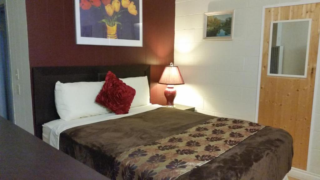 A bed or beds in a room at West Castle Motel