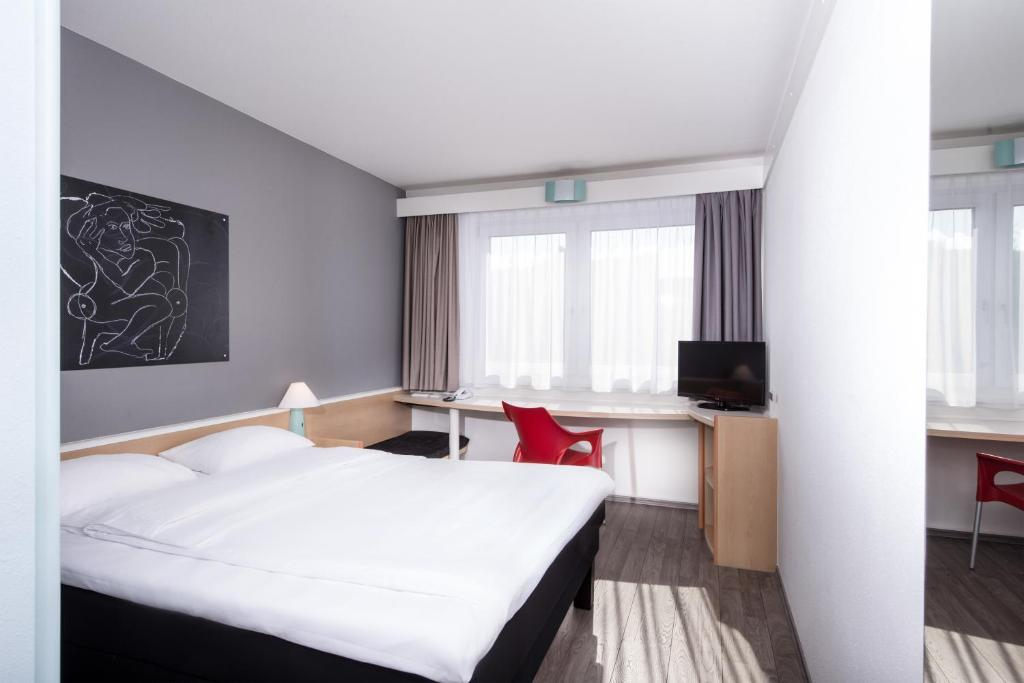 A bed or beds in a room at ibis Hotel Berlin Airport Tegel