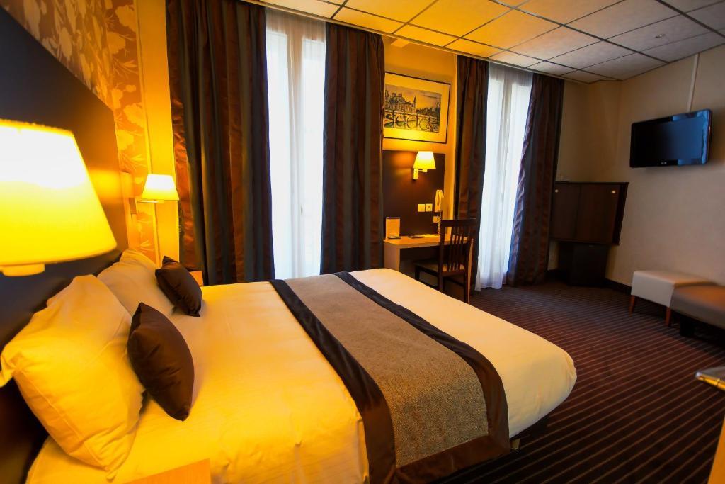 A bed or beds in a room at Hôtel Des Trois Gares