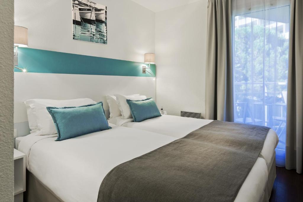 Кровать или кровати в номере Citadines Castellane Marseille