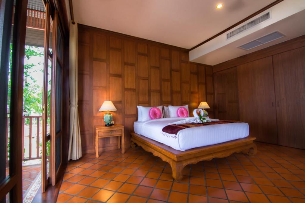 Baan Thai Lanta Resort tesisinde bir odada yatak veya yataklar