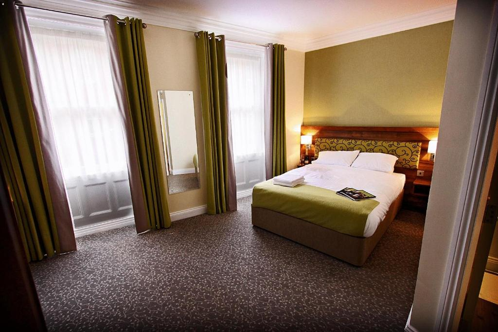 A bed or beds in a room at Surtees Hotel