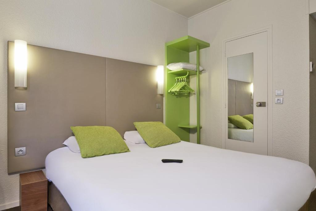 A bed or beds in a room at Campanile Paris Ouest - Porte de Champerret Levallois