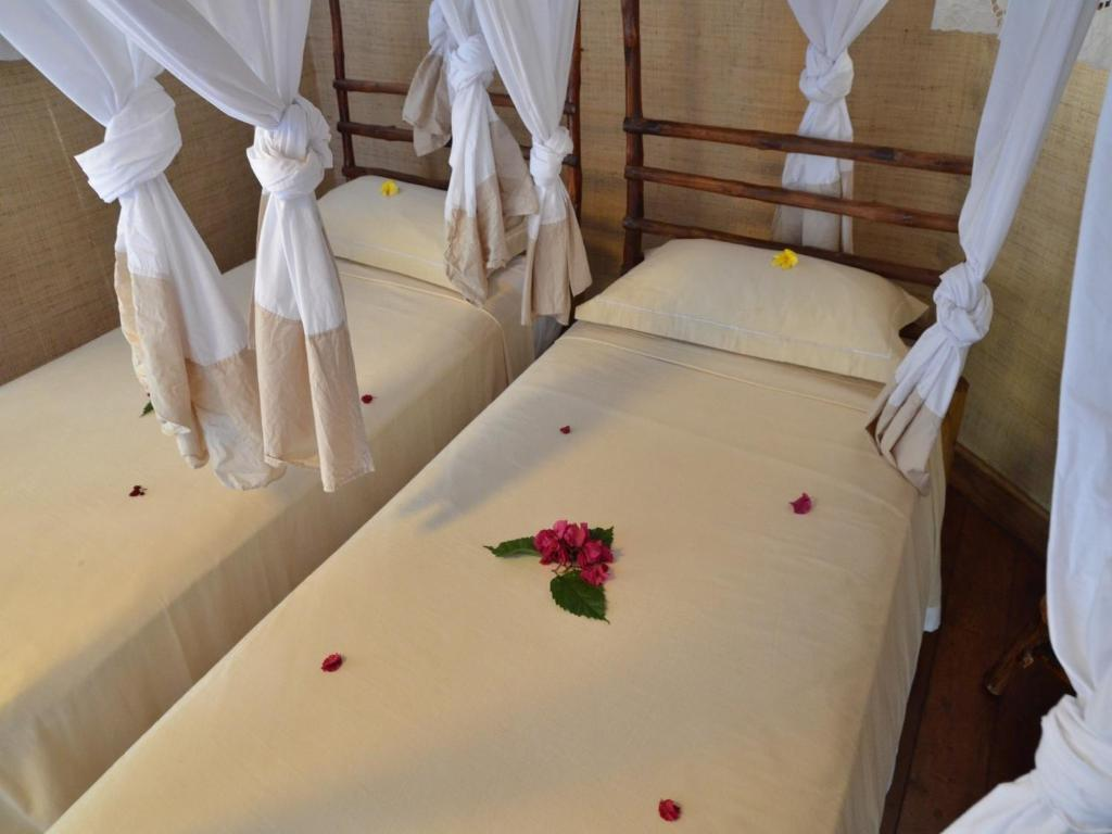 A bed or beds in a room at Auberge Le Maki Lodge