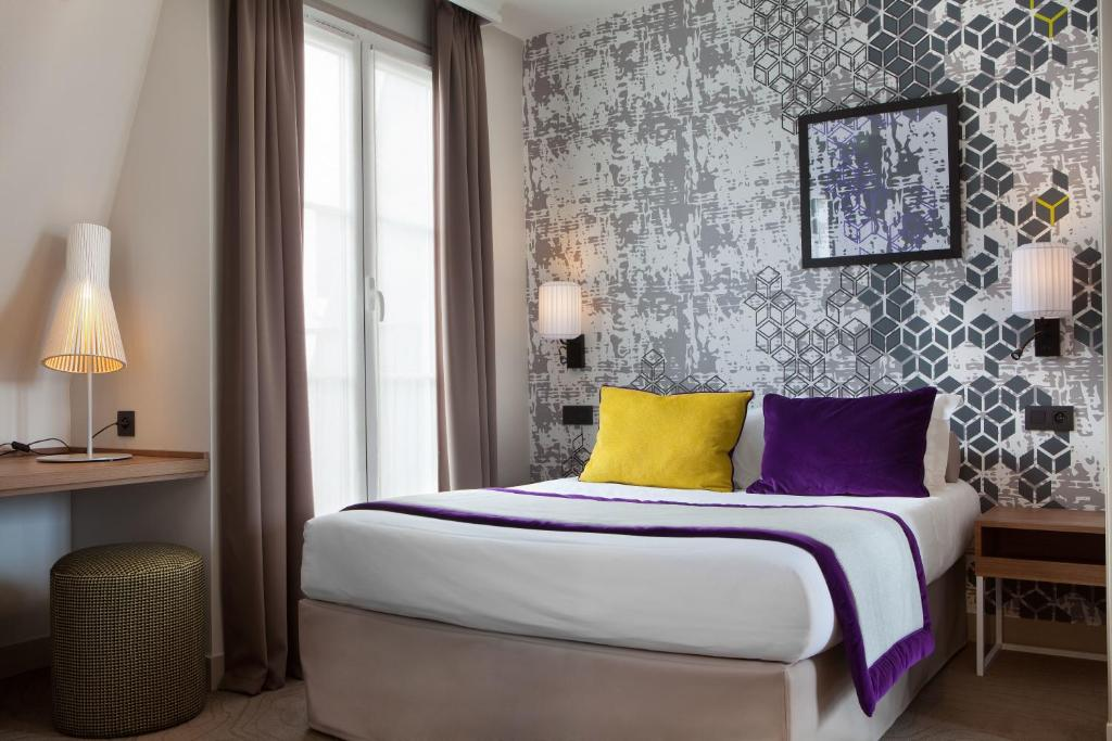 A bed or beds in a room at Hotel des Nations Saint Germain