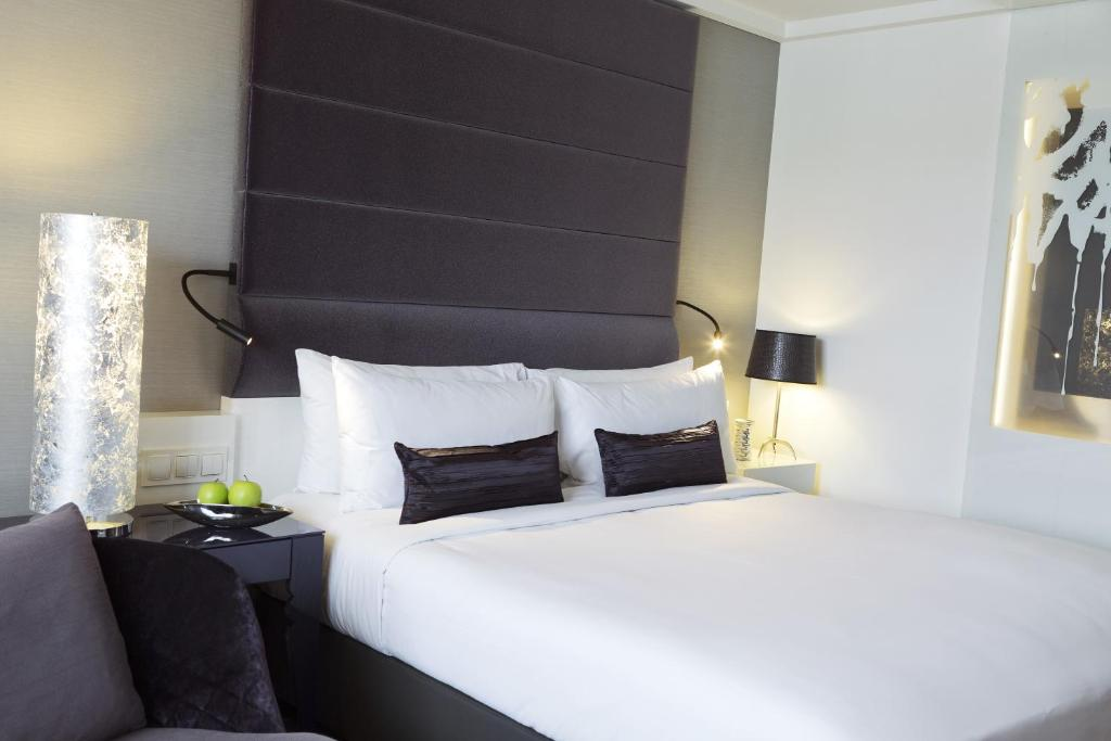 A bed or beds in a room at Renaissance Wien Hotel