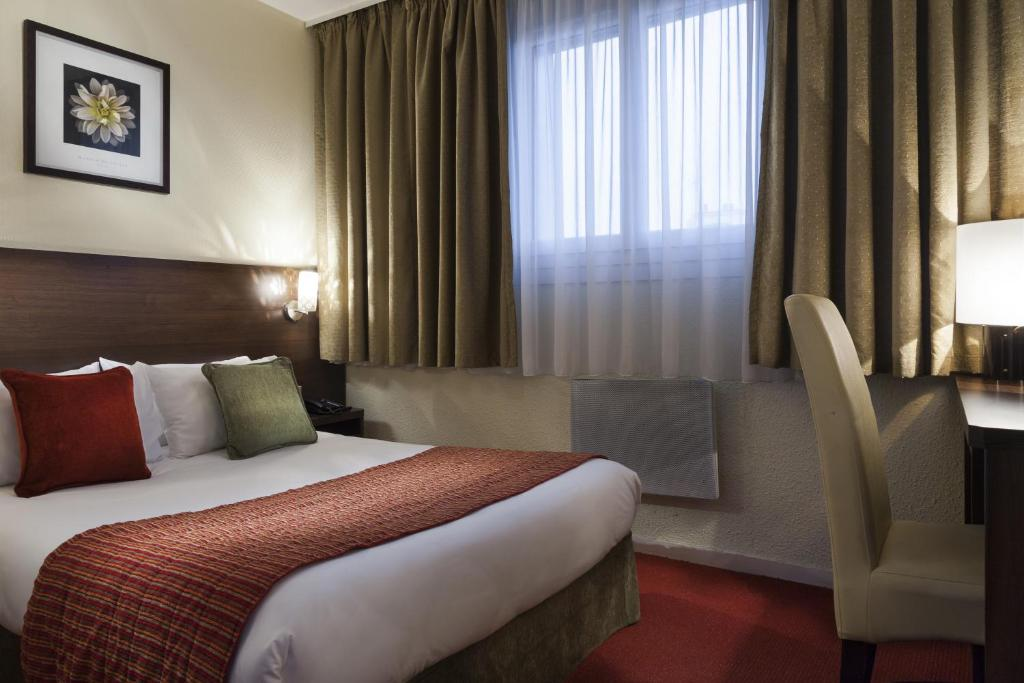 A bed or beds in a room at The Originals City, Hôtel Paris Sud, Orly-Draveil (Inter-Hotel)