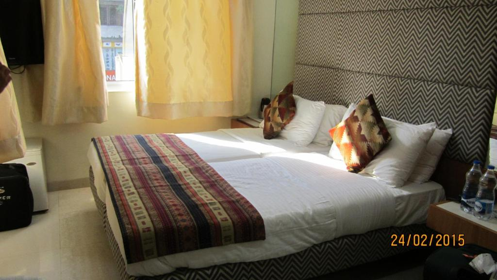 A bed or beds in a room at Empire Hotel - Grant Road
