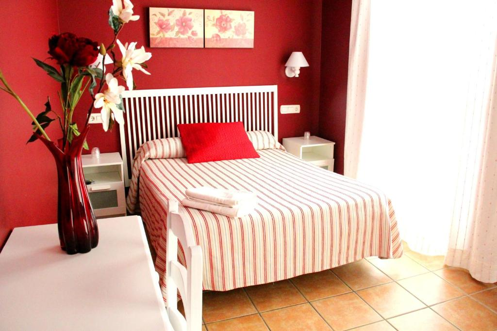 A bed or beds in a room at Hostal Mena