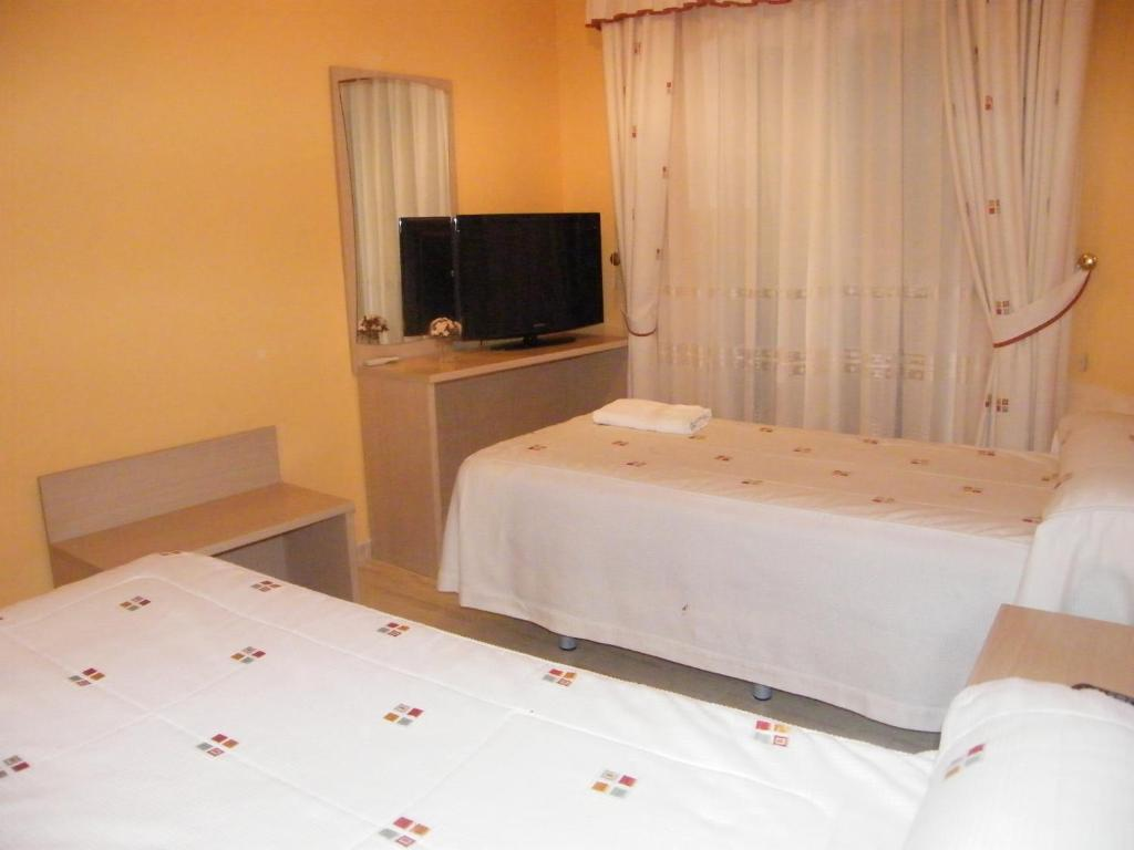 A bed or beds in a room at Hostal Dulcinea