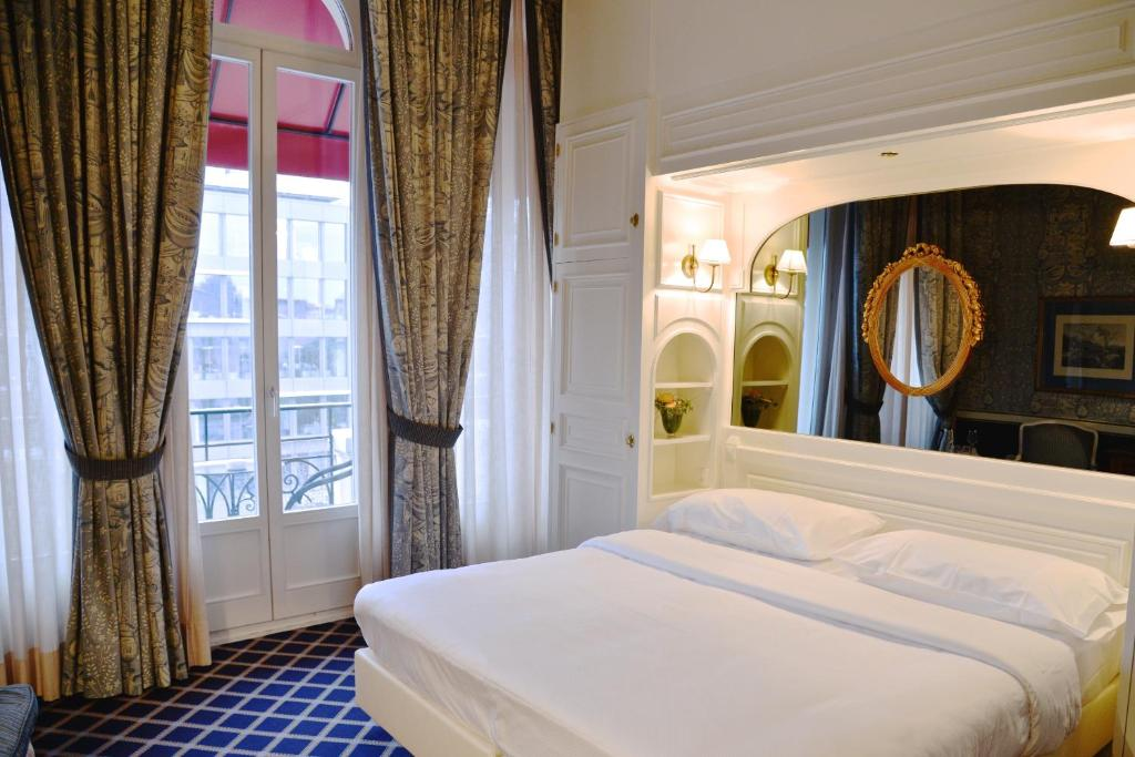 A bed or beds in a room at Carlton Lausanne Boutique Hôtel