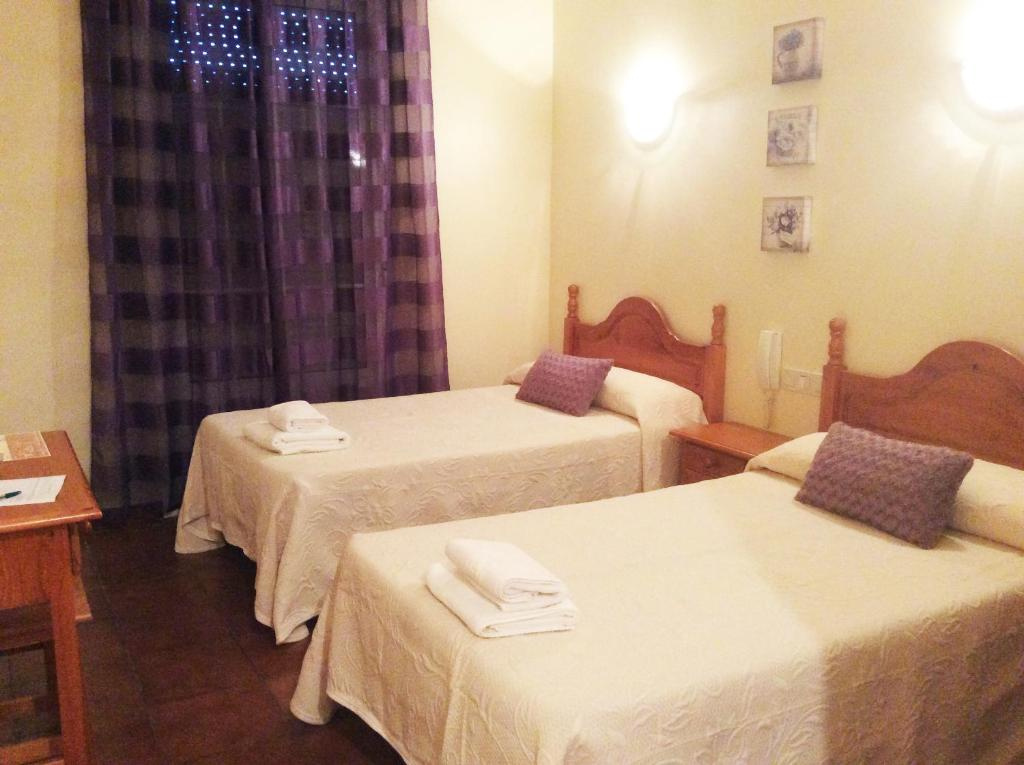 A bed or beds in a room at Hostal El Chiringuito