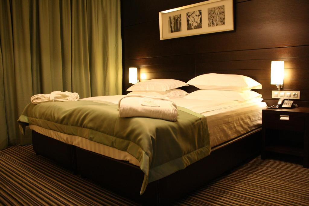 A bed or beds in a room at Olives City Hotel