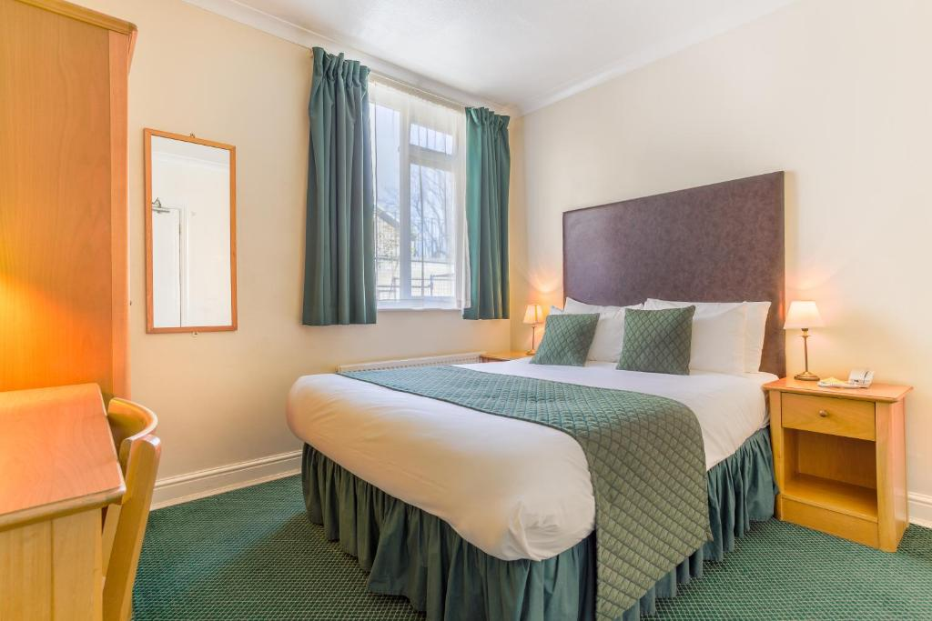 A bed or beds in a room at London Town Hotel