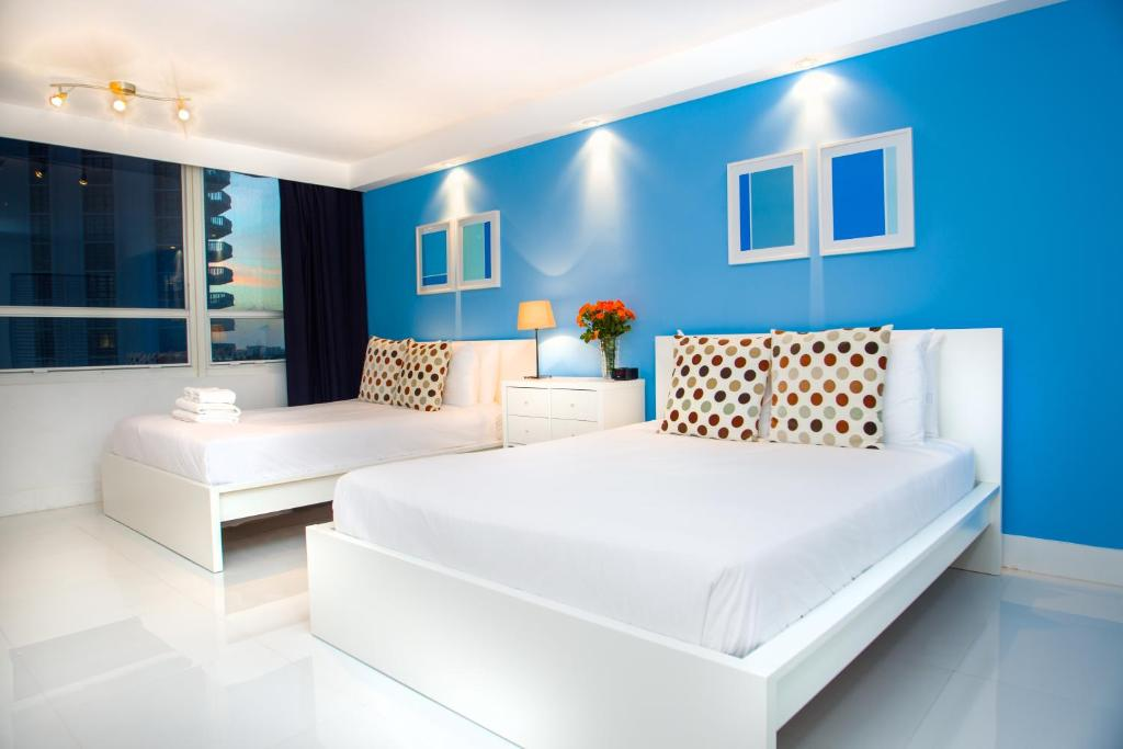 A bed or beds in a room at Beach Apartments by Design Suites