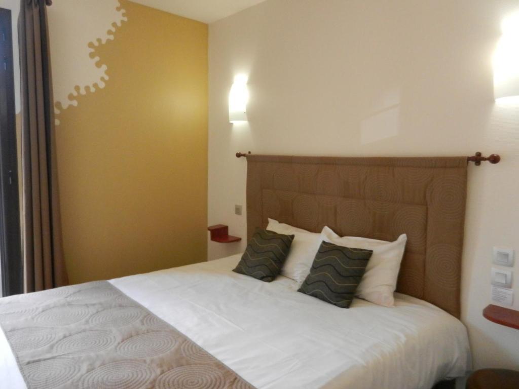 Un ou plusieurs lits dans un hébergement de l'établissement Logis L'Hôtel
