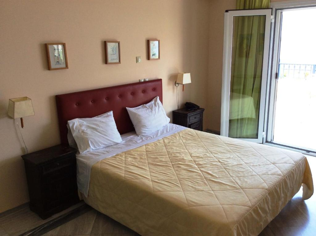 A bed or beds in a room at Angelica Villas Hotel Apartments