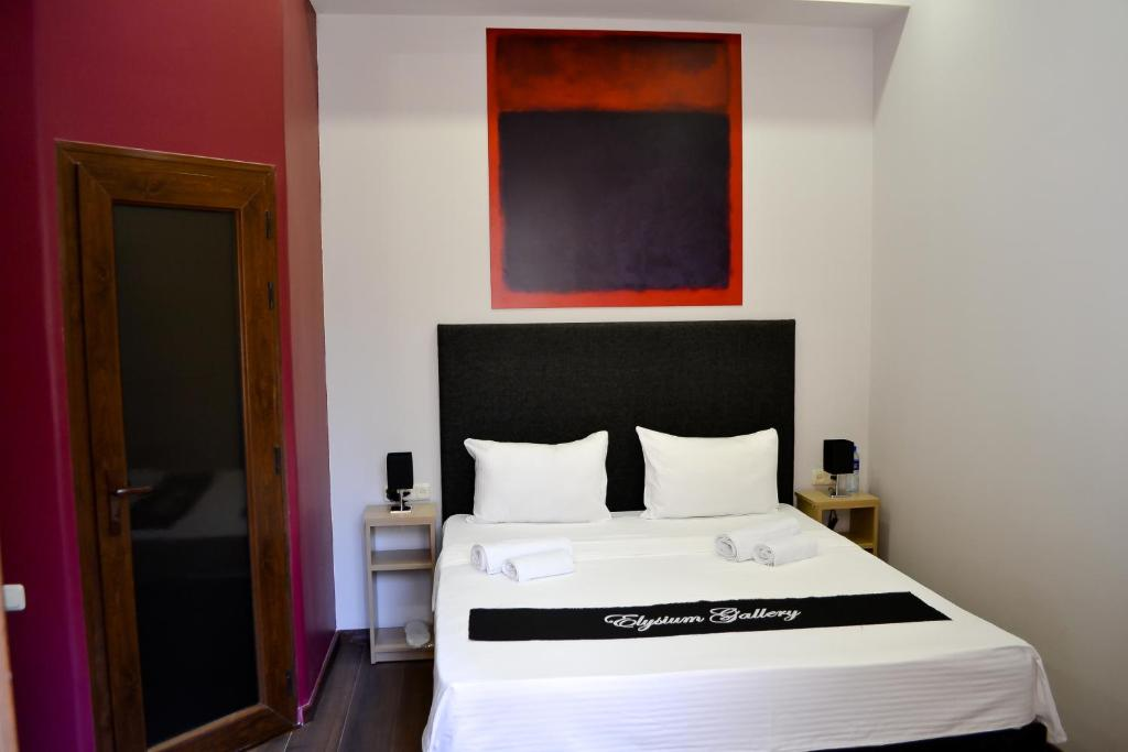 A bed or beds in a room at Elysium Gallery Hotel