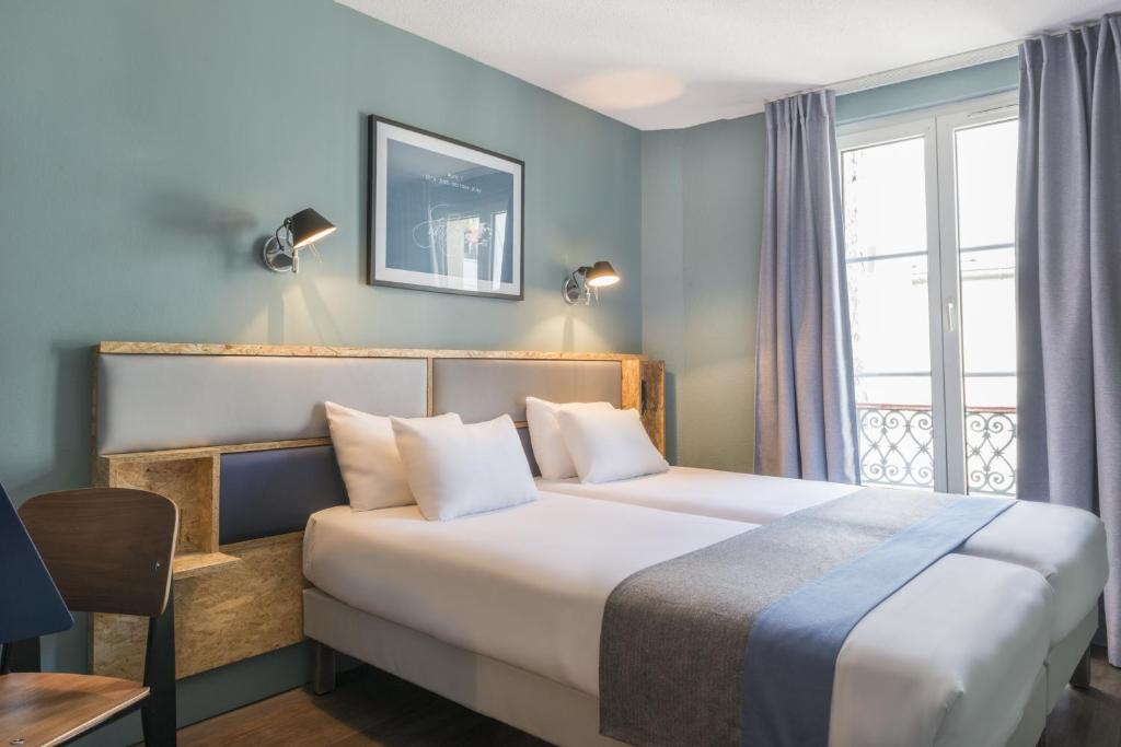 A bed or beds in a room at Hôtel Basss