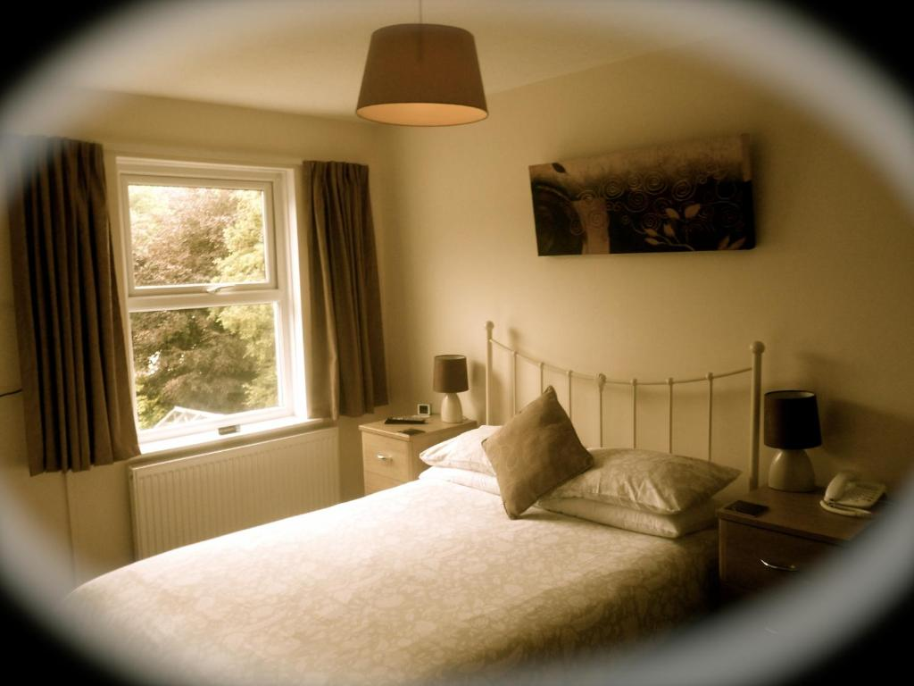 A bed or beds in a room at Strathallan Guest House