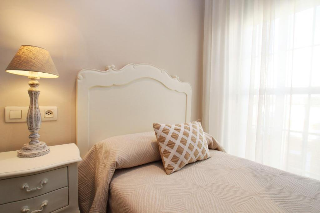 A bed or beds in a room at Hotel Maestranza