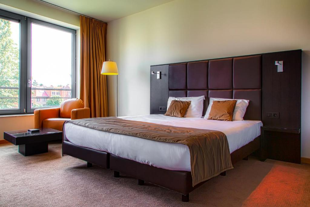 A bed or beds in a room at Diamant Suites Brussels EU