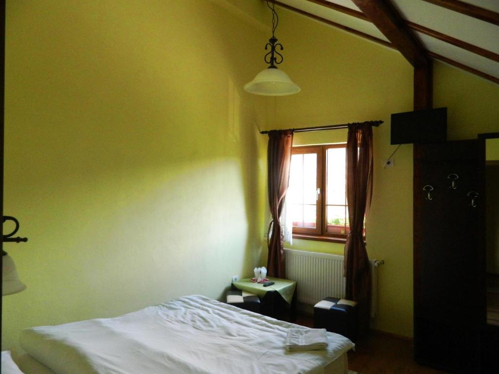Un pat sau paturi într-o cameră la Hanul cu Noroc
