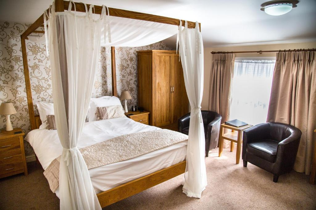 A bed or beds in a room at Stoneybeck Inn