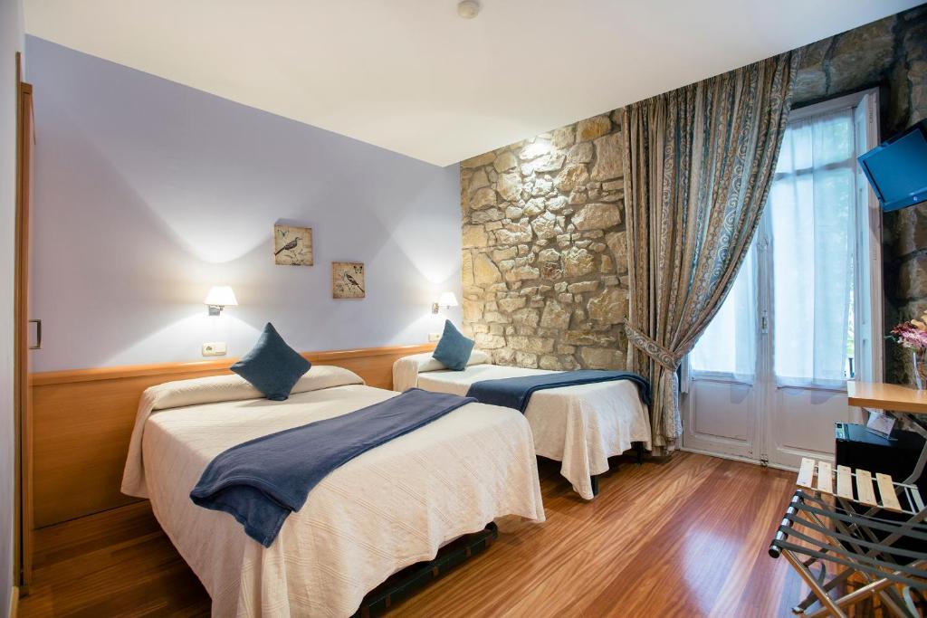 A bed or beds in a room at Pensión Nuevas Artes