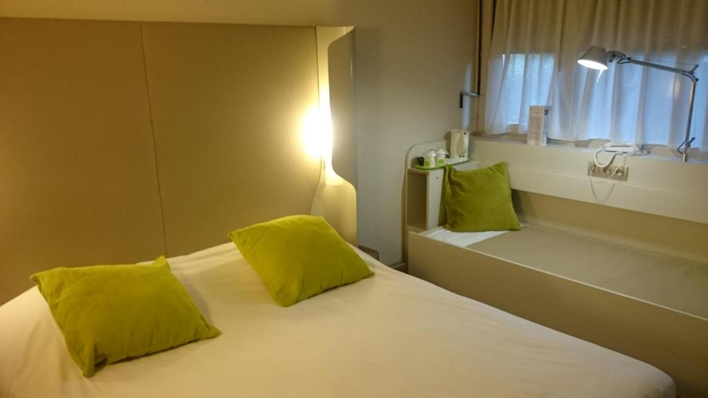 A bed or beds in a room at Campanile Bayonne