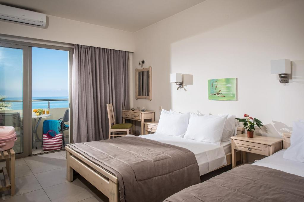 A bed or beds in a room at Malliotakis Beach Hotel