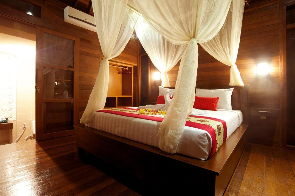 A bed or beds in a room at Saka Village Resort Ubud