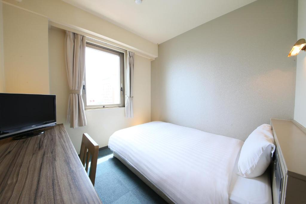 A bed or beds in a room at Hotel Wing International Hitachi