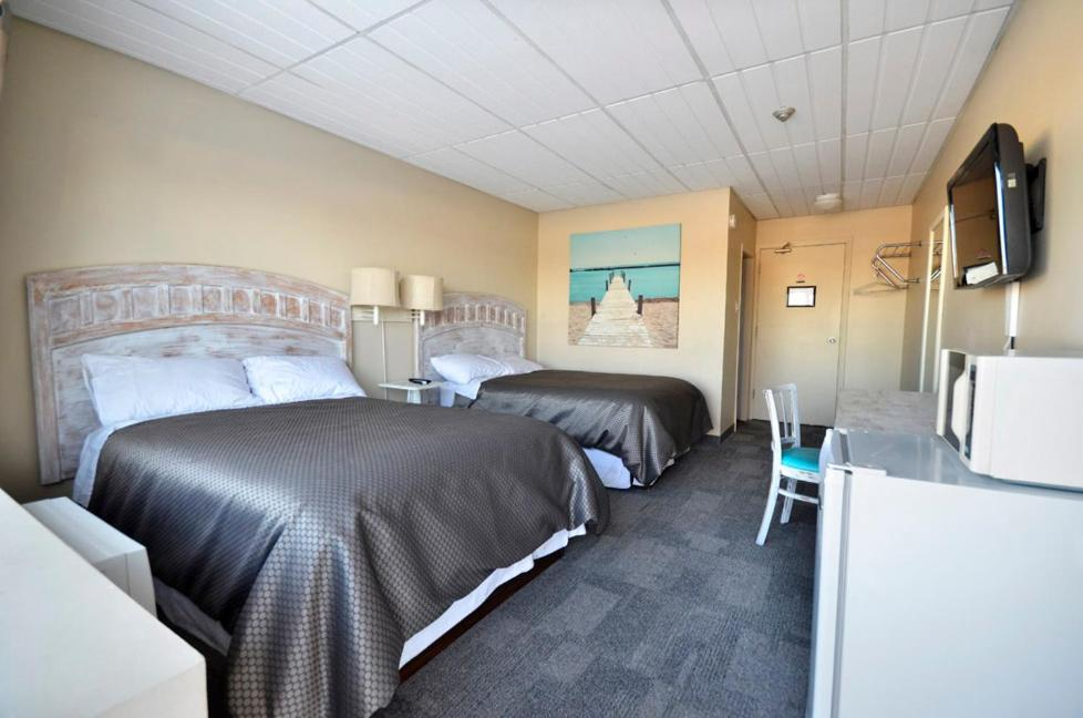 A bed or beds in a room at St. Norbert Hotel