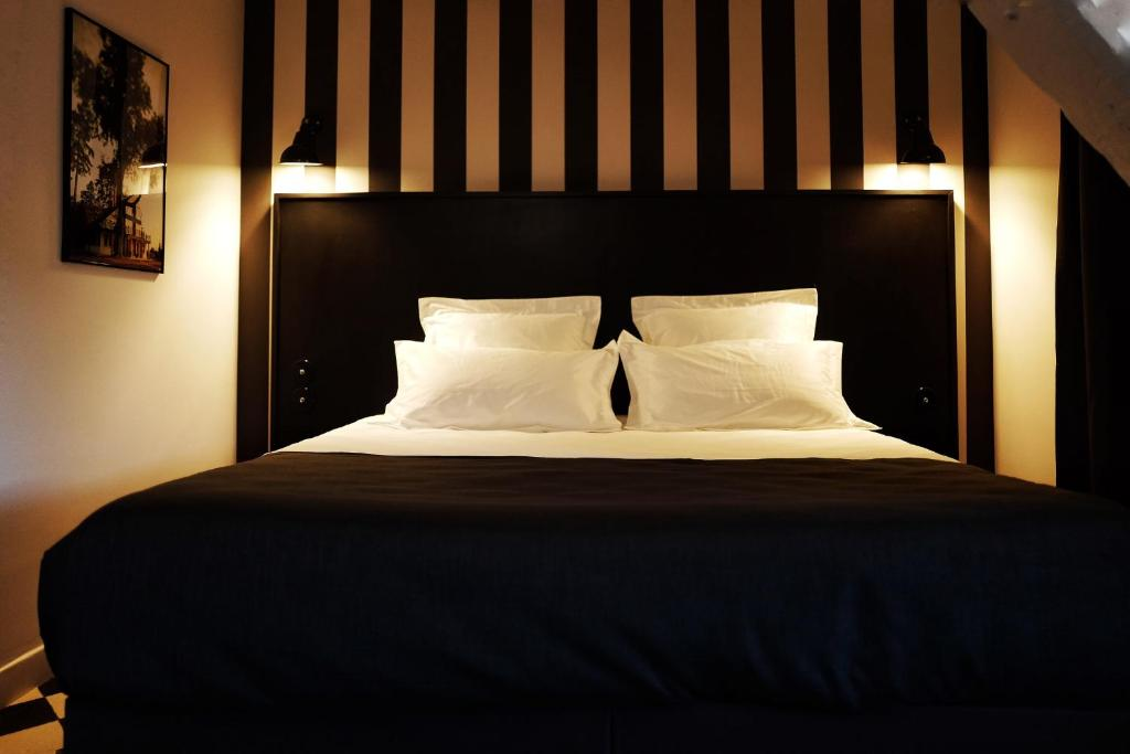 A bed or beds in a room at Hotel des Carmes