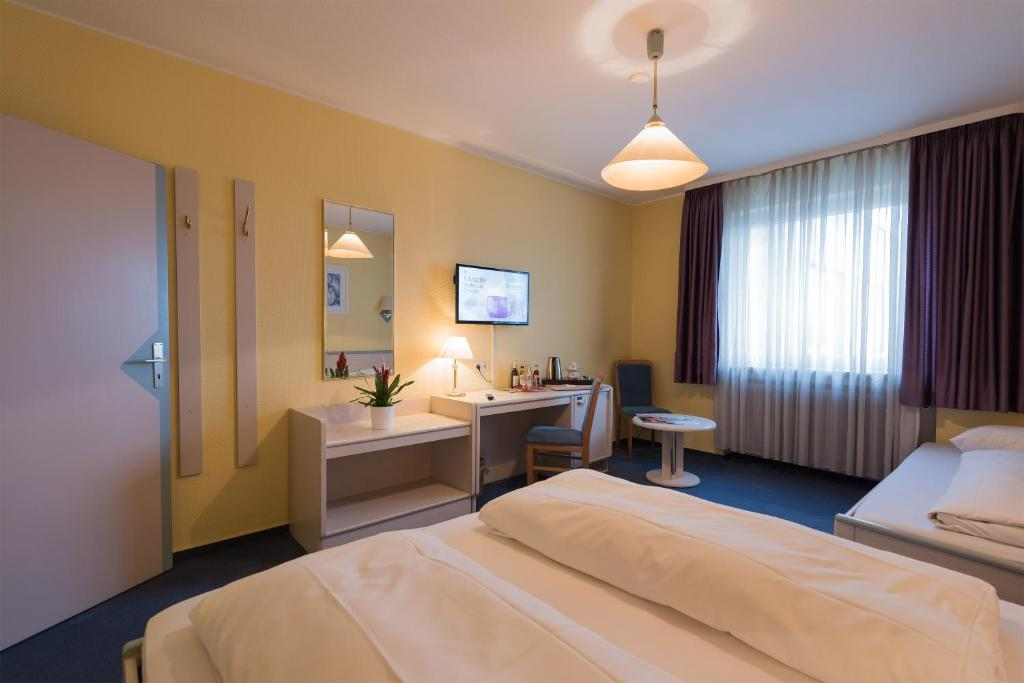 A bed or beds in a room at Tagungshotel Höchster Hof