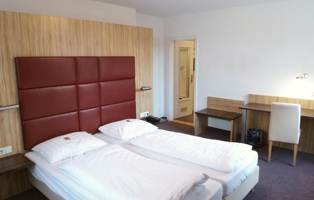 A bed or beds in a room at Hotel & Gasthaus Backmulde