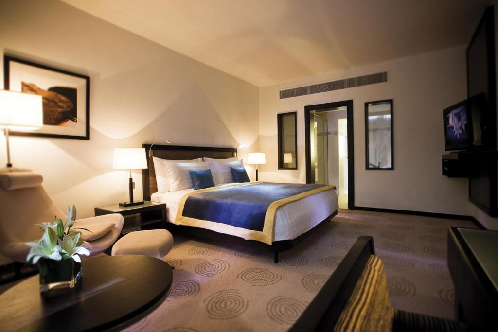 A bed or beds in a room at Avani Deira Dubai Hotel