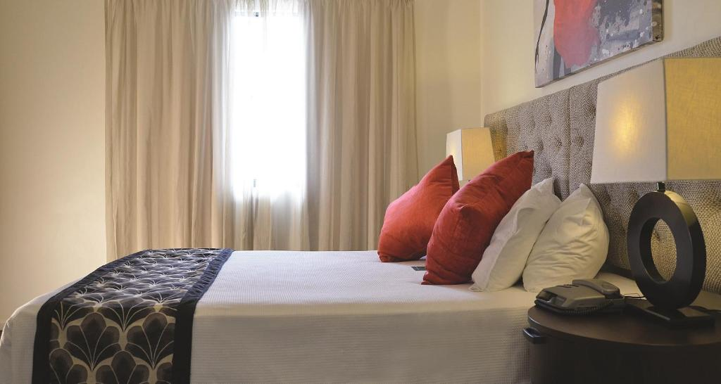 A bed or beds in a room at Metro Advance Apartments & Hotel