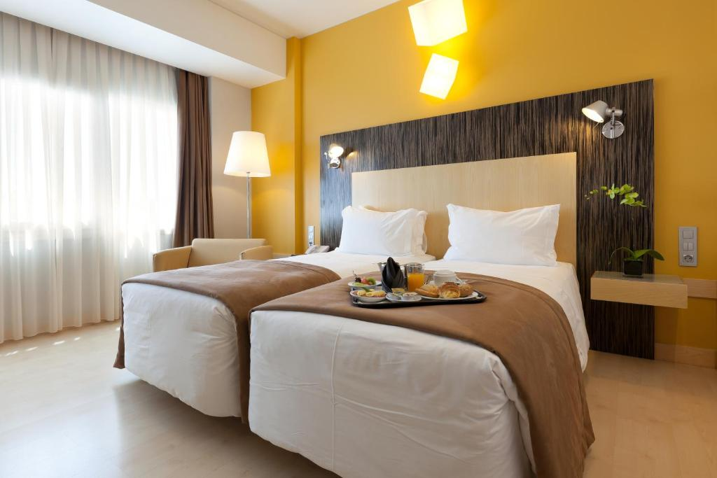A bed or beds in a room at Hotel Alif Avenidas