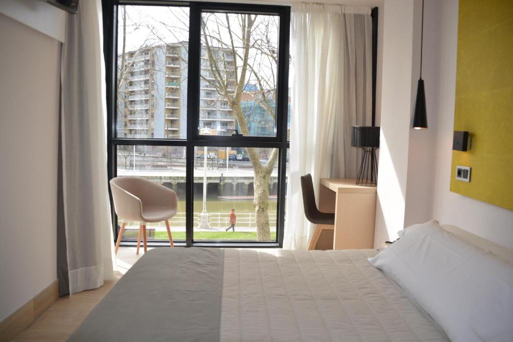 A bed or beds in a room at Hotel Bilbao Plaza