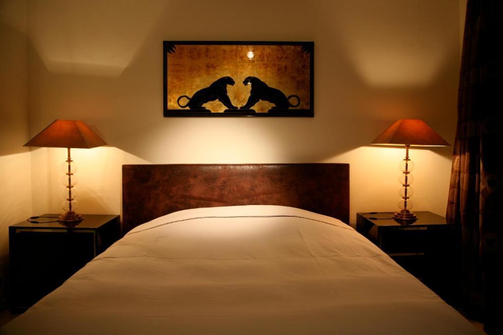 En eller flere senge i et værelse på Sablon-Aire Suite