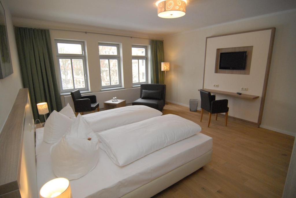 A bed or beds in a room at Hotel Pension am Goethehaus