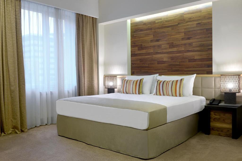 Een bed of bedden in een kamer bij Minotel Barsam Suites