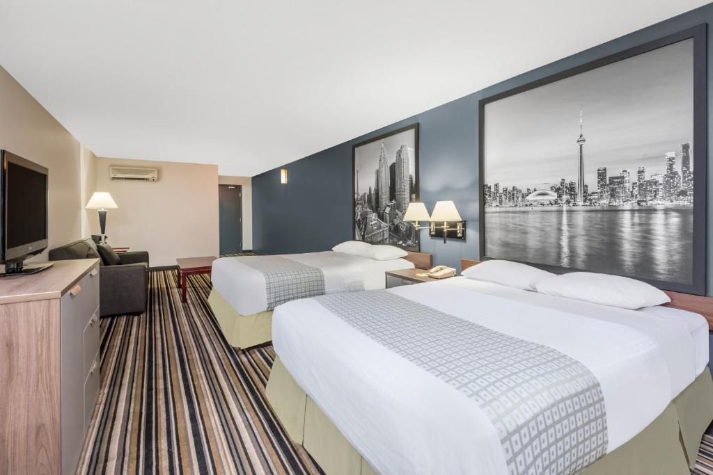 A bed or beds in a room at Super 8 by Wyndham Downtown Toronto