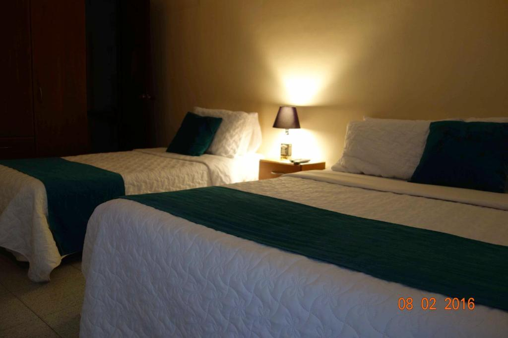 A bed or beds in a room at Hotel Maceo 55 - Colonial Inn