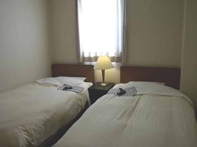 A bed or beds in a room at Business Daiichi Hotel