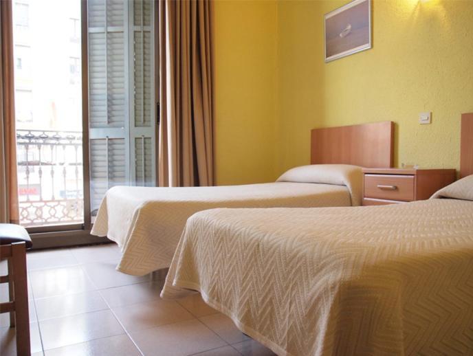 Ein Bett oder Betten in einem Zimmer der Unterkunft Hostal Delfos