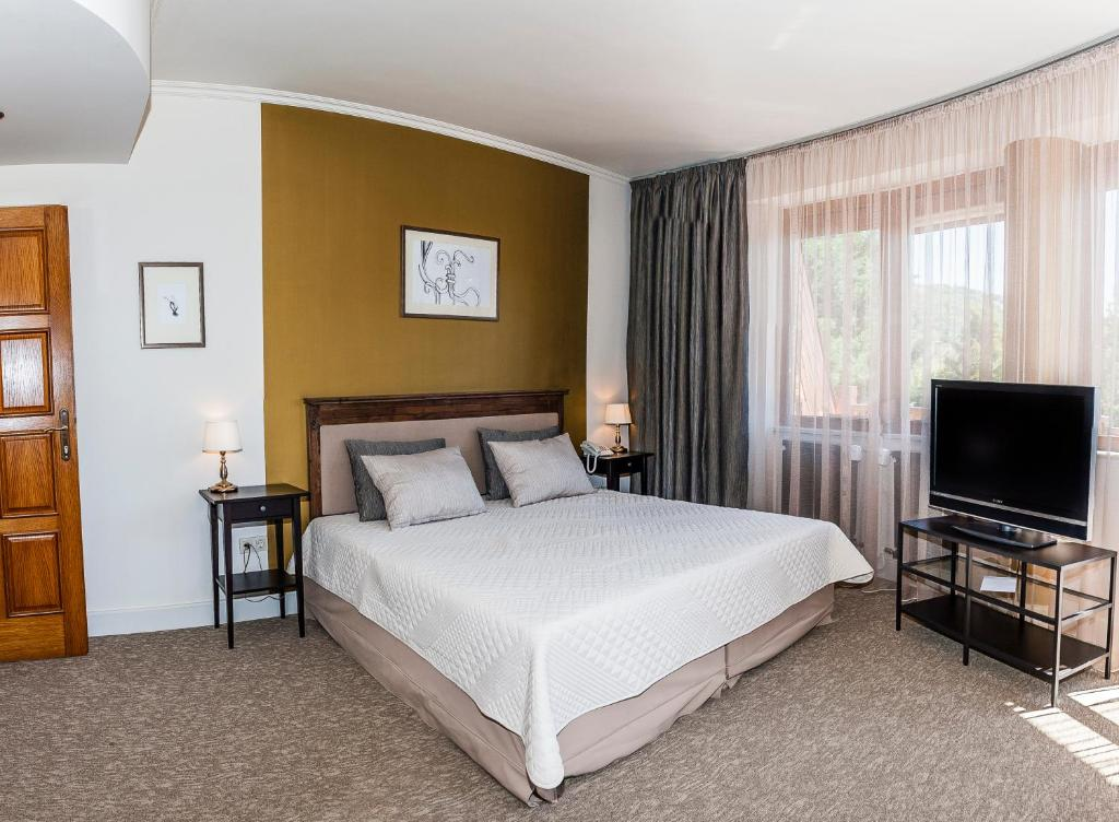 A bed or beds in a room at Villa Rosa Boutique Hotel
